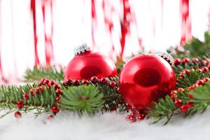 two red spherical christmas ornaments surrounded by christmas tree branches and red beads