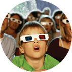 small kid surrounded by people all wearing 3D glasses watching a 3D movie at our Skylon Theatre