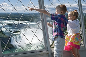 Two small kids enjoying the view from the observation deck at Skylon Tower