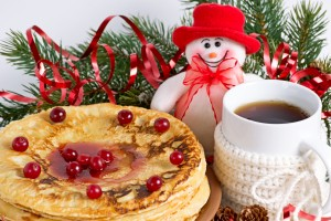 Christmas composition with pancakes, cup of tea and snowman