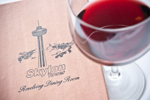 a skylon tower revolving dining room menu closed and paired with a tall glass of red wine.