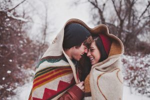 winter couple under a blanket outside a snow storm