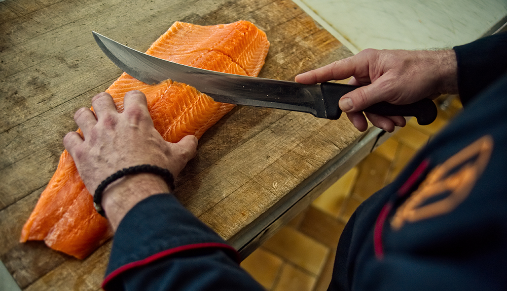 Chef preparing Salmon for the Revolving Dining Room